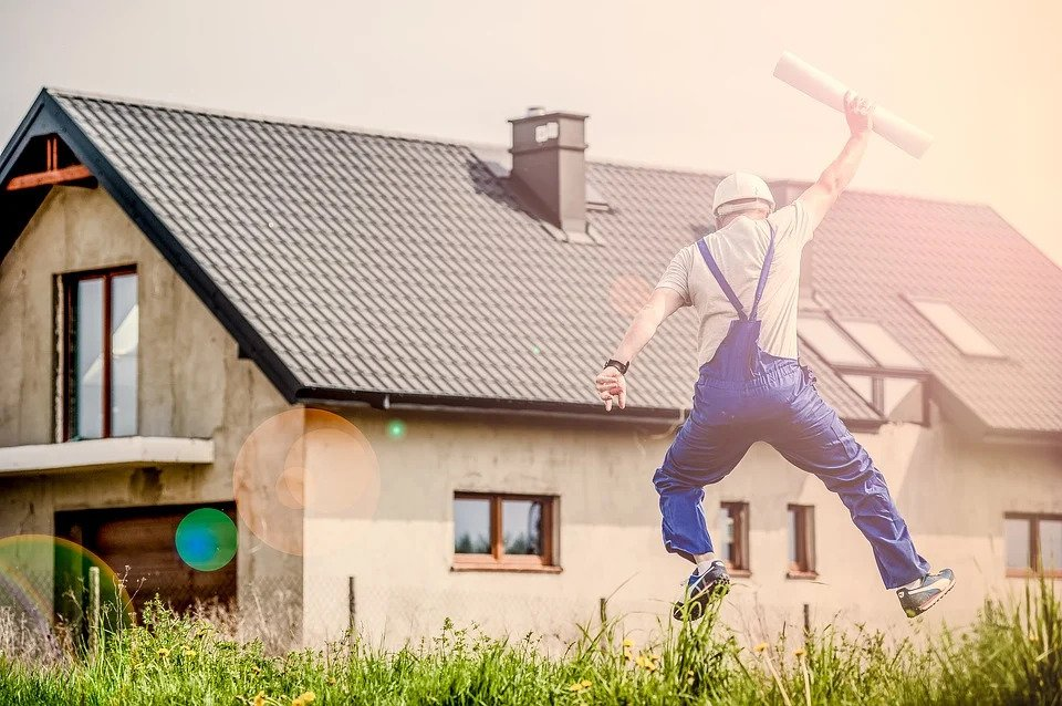 man in front of house jumping